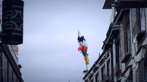 Chiuda in su della bandierina del tibet sulla parte superiore dell'edificio