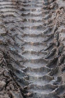 Close-up pneumatico tracce camion su una strada sterrata alla luce del giorno.