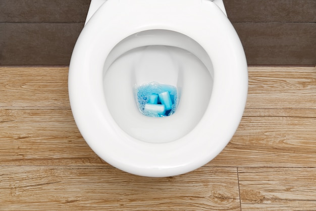 Primo piano di una toilette intasato con prodotti per l'igiene e carta igienica.