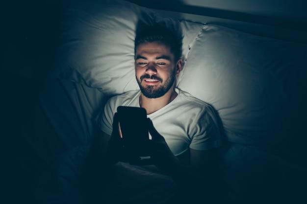 Primo piano in alto sopra il ritratto di vista di alto angolo del suo lui bello attraente brunet allegro allegro ragazzo sdraiato a letto usando il tempo libero della cella chiacchierando di notte a tarda sera casa stanza illuminata scura