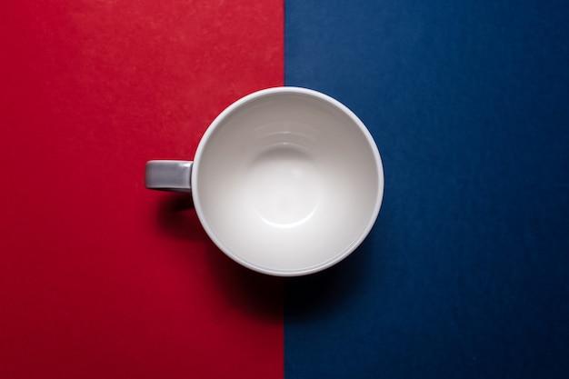 Close-up vista dall'alto della tazza da tè in ceramica su sfondo a trama di pareti rosse e blu.
