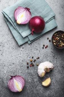 Primo piano, vista dall'alto di cipolle rosse fresche crude tagliate, aglio e condimenti su fondo rustico in pietra grigia. cucina, cibo vegetariano o concetto di alimentazione sana, cibo biologico pulito