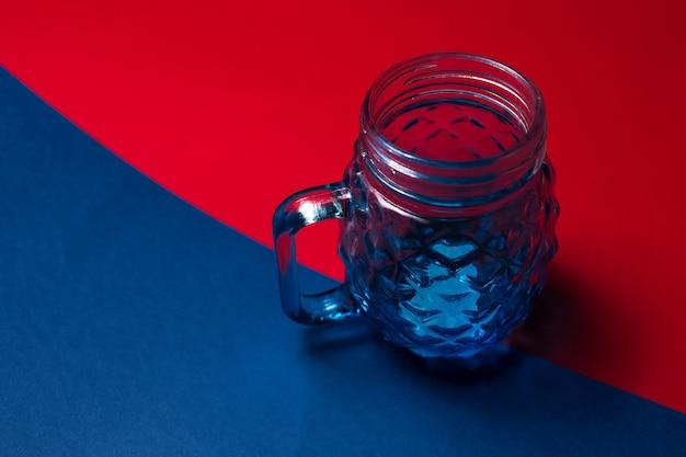 Vista dall'alto del primo piano della tazza di vetro per il succo su due sfondi con texture di colori rosso e blu.
