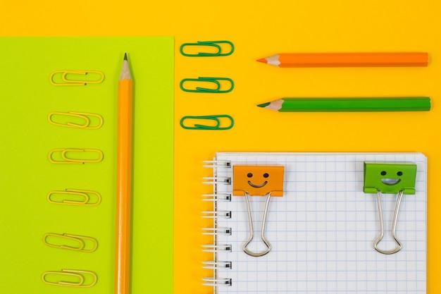 Close up vista dall'alto foto di materiale scolastico. set di blocco note a spirale, clip e matite su sfondo giallo e verde
