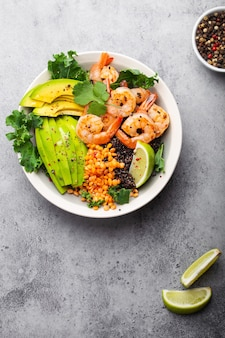 Primo piano, vista dall'alto dell'insalatiera con gamberetti, avocado, cavolo riccio fresco, quinoa, lenticchie rosse, lime e olio d'oliva su sfondo grigio pietra. ciotola per il pranzo, un'alimentazione sana e pulita, una dieta o un concetto nutrizionale