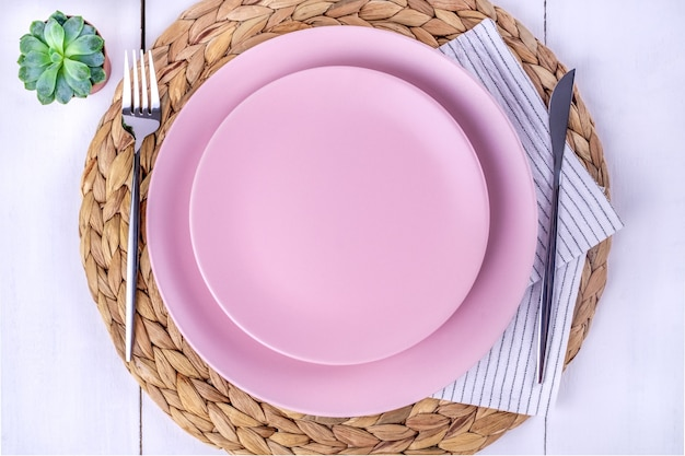Primo piano vista dall'alto di una porzione di due piatti rosa vuoti, un coltello e una forchetta su un tovagliolo ecologico di paglia. messa a fuoco selettiva. mockup, minimalismo.