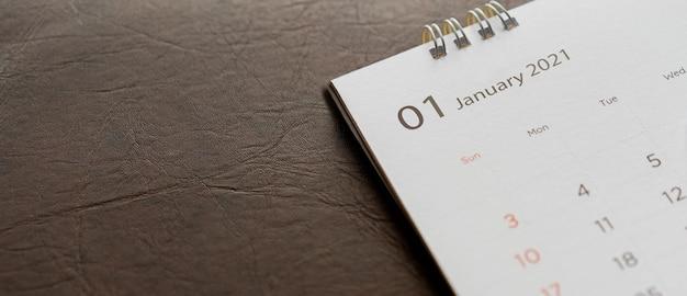 Primo piano vista dall'alto sul calendario 2021 calendario bianco su sfondo di pelle marrone