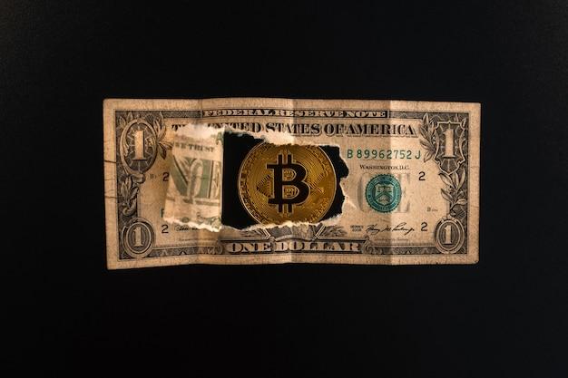 Primo piano: una banconota da un dollaro strappata attraverso la quale sono visibili le monete bitcoin. finanza e affari
