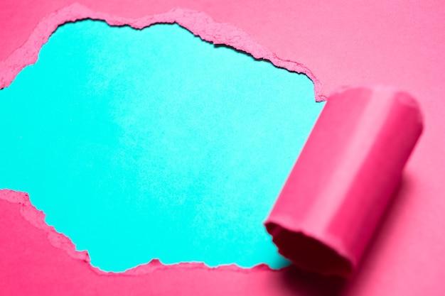 Close-up di carta rosa strappata con spazio per il testo di sfondo azzurro.