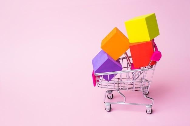 Primo piano carrello della spesa in metallo giocattolo con manico in plastica rossa e scatole multicolori all'interno sul retro rosa