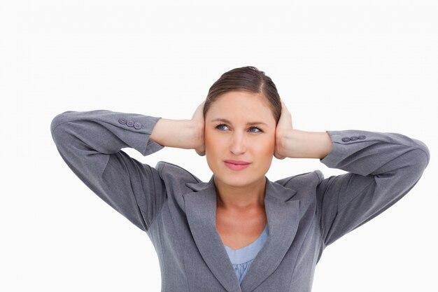 Chiuda in su della tradeswoman che copre le sue orecchie