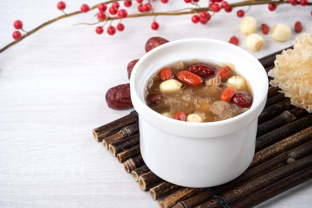 Chiuda in su della zuppa di funghi bianca neve dolce cinese tradizionale con semi di loto, datteri rossi (giuggiola) e wolfberry (bacche di goji, gojiberry) su sfondo bianco.