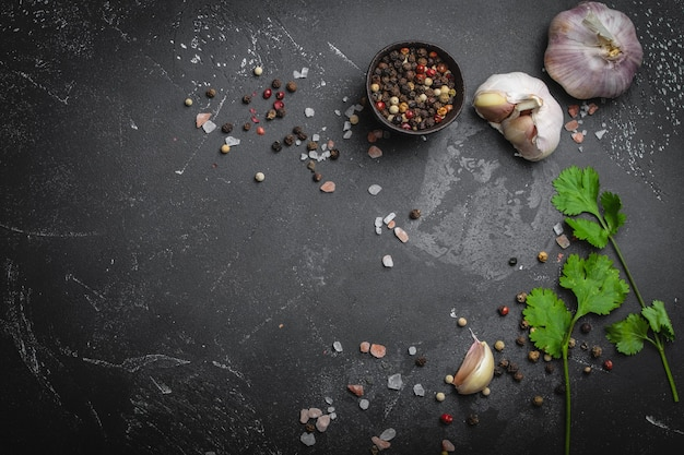 Primo piano di ingredienti da cucina tradizionali: aglio, olio d'oliva, sale, pepe, erbe fresche su fondo rustico scuro. cornice per alimenti, concetto per cucinare cibi sani con spazio per il testo, vista dall'alto