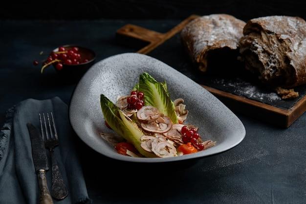 Primo piano sulla cucina tradizionale italiana vitello tonnato un piatto con carne di vitello in salamoia con salsa di crema di tonno e pane sulla tavola di legno
