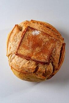 Primo piano di un tradizionale pane italiano rotondo su sfondo bianco.