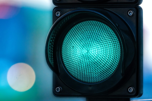 Primo piano del semaforo di traffico con luce verde su priorità bassa defocused della via della città con lo spazio della copia
