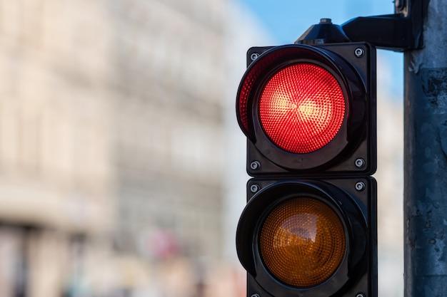 Primo piano del semaforo del traffico con luce rossa su priorità bassa defocused strada della città con lo spazio della copia