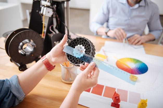 Primo piano di un righello trasparente nelle mani di una bella designer femminile mentre si lavora al suo progetto