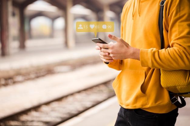 Viaggiatore del primo piano che per mezzo dello smartphone
