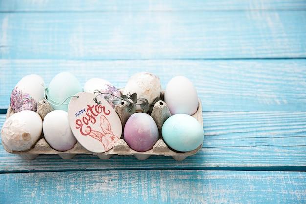 Primo piano di un vassoio con le uova di pasqua festive su uno spazio di copia superficie in legno. felice pasqua concetto.