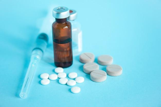 Primo piano di trattamenti per la siringa di malattia, tablet e flaconcino di medicina. medicinali per la vaccinazione e il trattamento delle malattie.