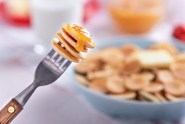 Close up trendy minuscole frittelle cereali sulla forcella contro il piatto di frittelle