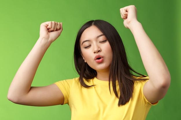 Primo piano trionfante carina donna asiatica spensierata che si diverte, balla con gioia, dimentica tutti i problemi che muovono musica ritmica, vittoria della pompa del pugno, celebrando notizie fortunate, chiudi gli occhi rilassati