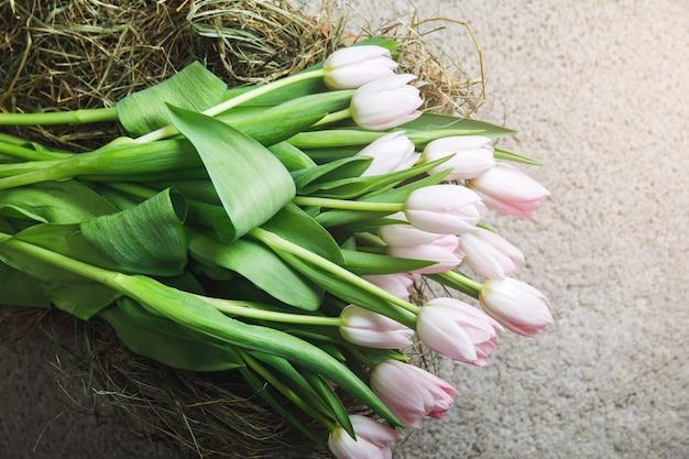 Il primo piano dei fiori dei tulipani nella scatola ha riempito di fieno