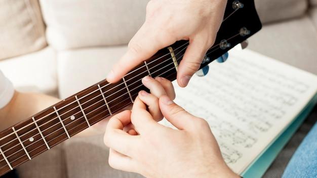 Tutor del primo piano che impara ragazzo a suonare la chitarra