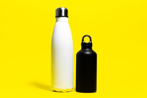 Close-up di due, in bianco e nero, in acciaio e alluminio, bottiglia d'acqua termica riutilizzabile su sfondo giallo.