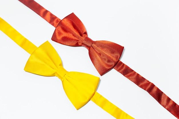 Close-up di due papillon di colori rosso e giallo isolato su bianco.