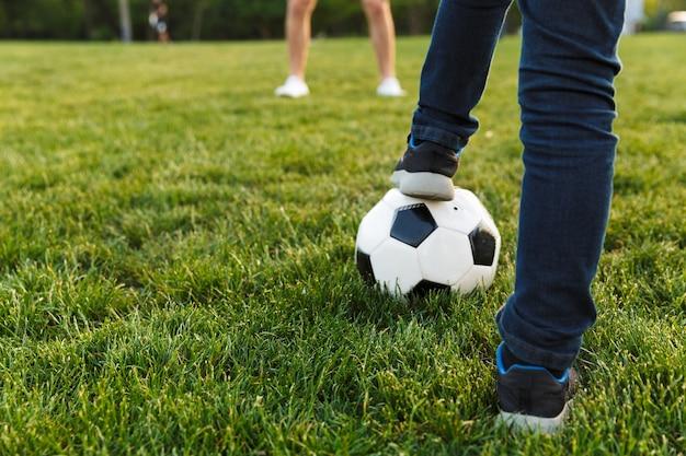 Primo piano di due fratelli che giocano a calcio sul prato del parco