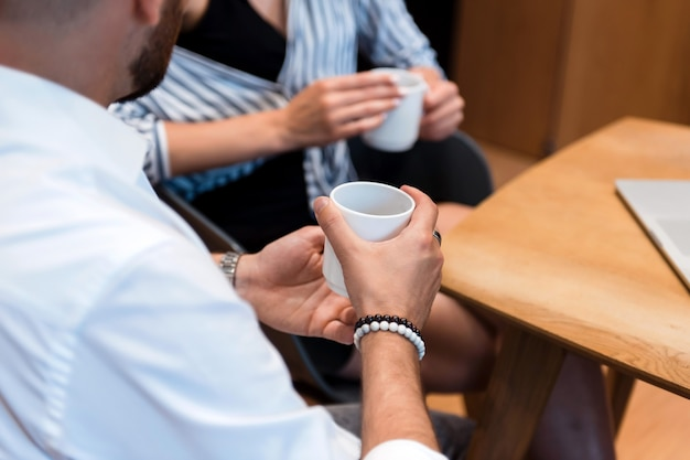 Primo piano di due partner commerciali in abbigliamento formale che discutono i momenti di lavoro davanti a una tazza di caffè