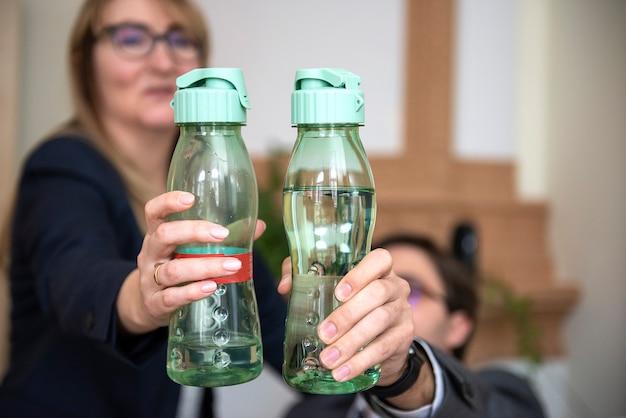 Un primo piano di due mani della gente di affari che tengono le bottiglie di acqua minerale di plastica