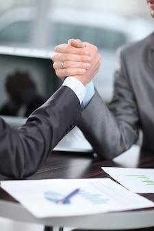 Avvicinamento. due uomini d'affari sono impegnati nel braccio di ferro a una scrivania.
