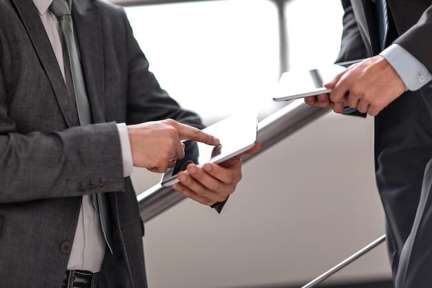 Avvicinamento. due uomini d'affari con tablet pc