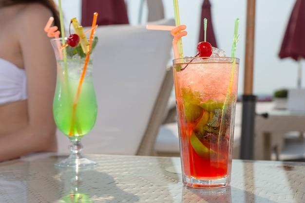 Close up di due colorate e rinfrescanti bevande tropicali in appoggio sul tavolo di vetro sul ponte soleggiato del lussuoso resort sulla spiaggia