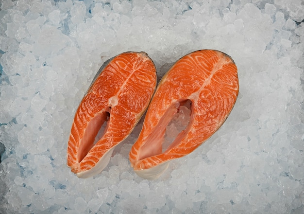 Chiudere due bistecche di pesce salmone crudo fresco su ghiaccio tritato, vista dall'alto in alto, direttamente sopra