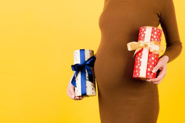 Primo piano di due scatole regalo nelle mani della donna incinta contro il suo ventre a sfondo giallo. e 'un ragazzo o una ragazza? in attesa di gemelli. copia spazio.