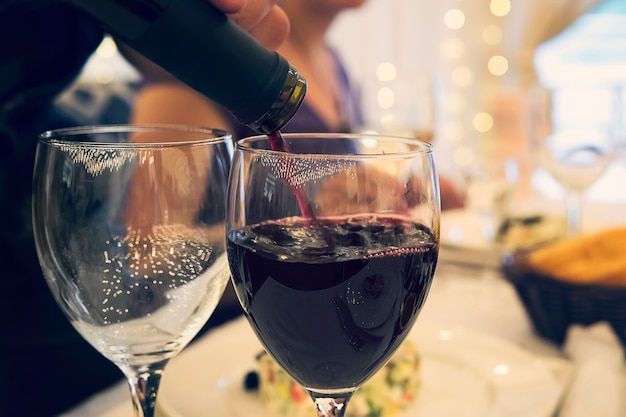 Primo piano di due bicchieri su un tavolo da ristorante con bicchieri a una cena formale. riempire il bicchiere di vino con vino rosso a un tavolo festivo. sommelier versa il vino rosso in un bicchiere.