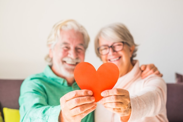 Primo piano di due anziani felici e innamorati che sorridono e guardano la telecamera tenendo insieme un cuore rosso - persone mature innamorate