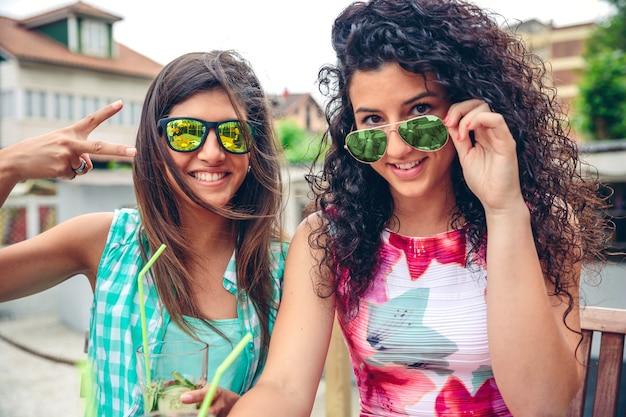 Primo piano di due giovani donne felici con occhiali da sole che sorridono e guardano la telecamera mentre tengono frullati di verdure verdi all'aperto