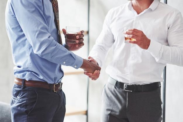 Primo piano di due uomini d'affari internazionali hanno un buon affare e tengono in mano bicchieri di whisky