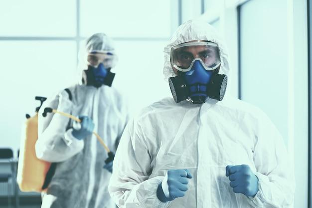 Avvicinamento. due disinfettanti maschili escono dalla stanza decontaminata. concetto di tutela della salute.