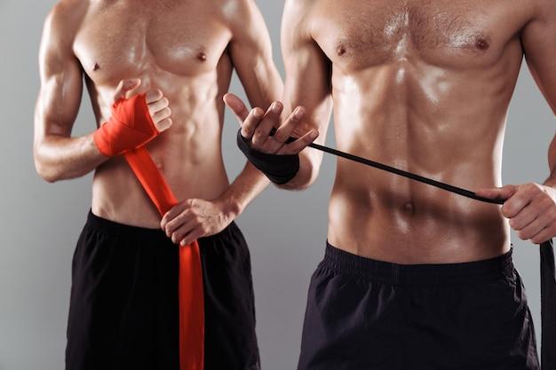 Primo piano di due fratelli gemelli muscolosi a torso nudo
