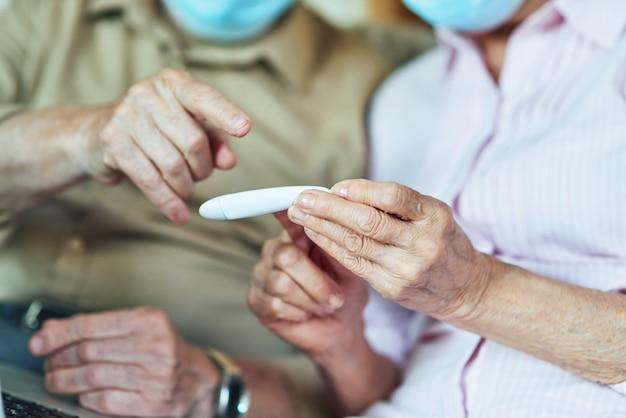 Primo piano di due pensionati che guardano il termometro