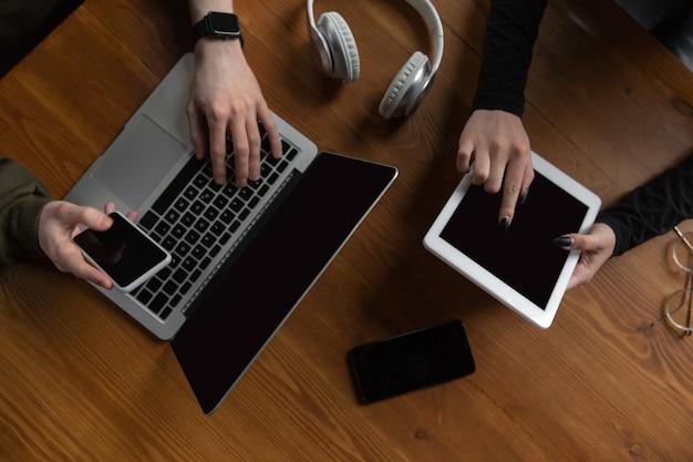 Primo piano di due persone, coppia che utilizza smartphone, laptop, smartwatch, istruzione e concetto di business, comunicazione durante l'autoisolamento. navigare, fare acquisti online, lavorare, studiare, chattare.