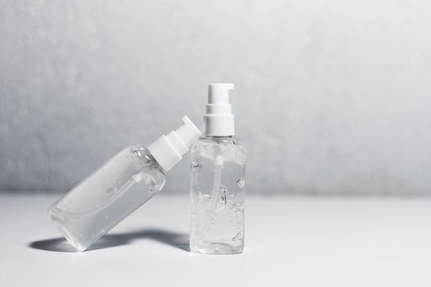 Primo piano di due bottiglie di plastica portatili con gel antisettico disinfettante sul tavolo bianco. superficie strutturata grigia.