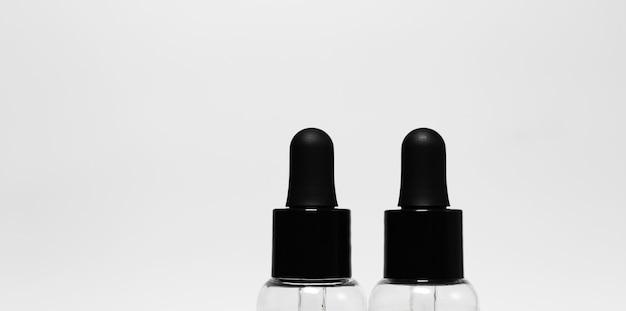 Primo piano di due bottiglie trasparenti con pipette nere isolate