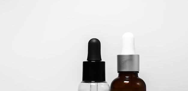 Close-up di due bottiglie trasparenti con pipette in bianco e nero isolato su bianco di sfondo per studio con copia spazio.